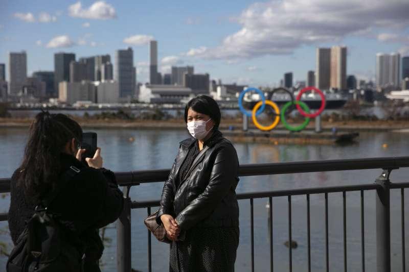 一位遊客帶著口罩在東京御台場跟奧運標誌合影。(美聯社)