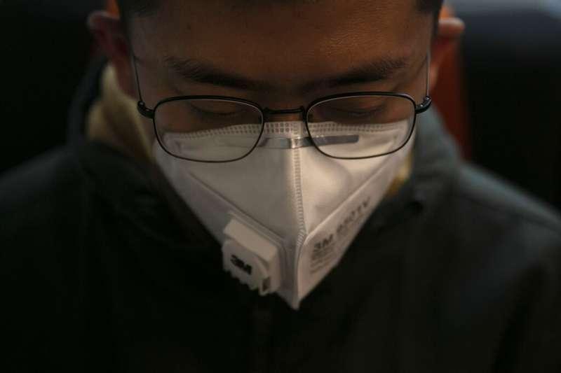 武漢肺炎,東京一位電車上的日本民眾正戴著口罩小憩。(美聯社)