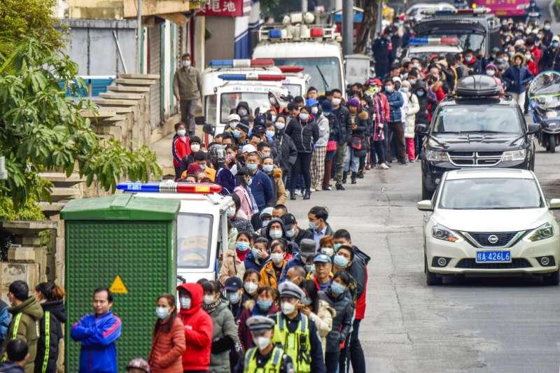 武漢肺炎疫情持續延燒,廣西南寧買口罩的民眾大排長龍。(美聯社)