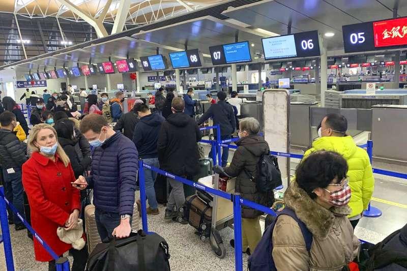 武漢肺炎疫情升高,北京首都機場的遊客也紛紛戴起口罩。(美聯社)