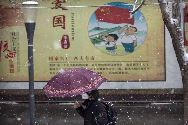 武漢肺炎蔓延全球,日、加等國首長為台灣被排拒為世衛大會門外抱屈。圖為疫配戴口罩的北京民眾走過政治宣傳標語前(AP)