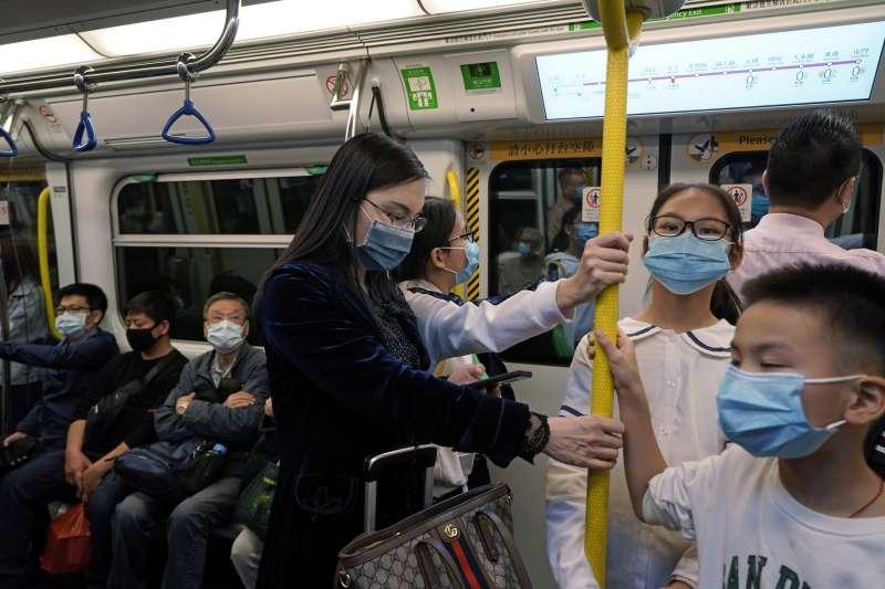 武漢肺炎疫情蔓延,1月23日,香港地鐵內的乘客大多戴著口罩(美聯社)
