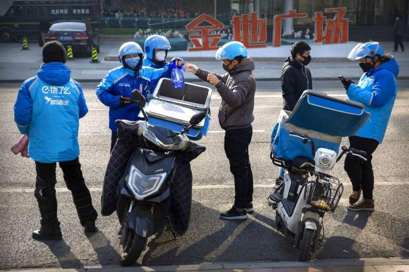 武漢肺炎疫情未歇,北京的外送員也戴起口罩自保。(美聯社)
