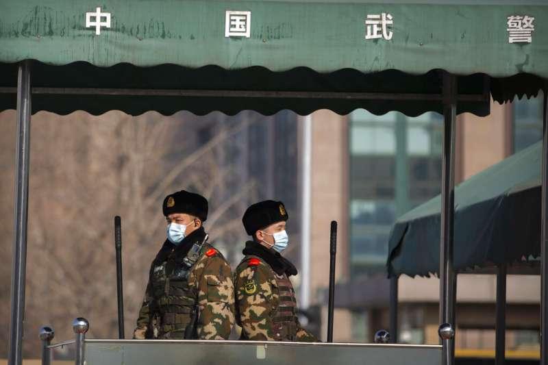 武漢肺炎疫情未歇,從台灣到國外都鬧口罩荒,圖為北京街頭的武警也戴起口罩自保。(美聯社)