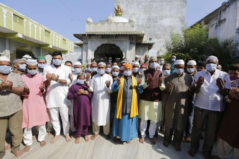 武漢肺炎疫情未歇,印尼一間清真寺的穆斯林帶著口罩祈求疫情緩和。(美聯社)