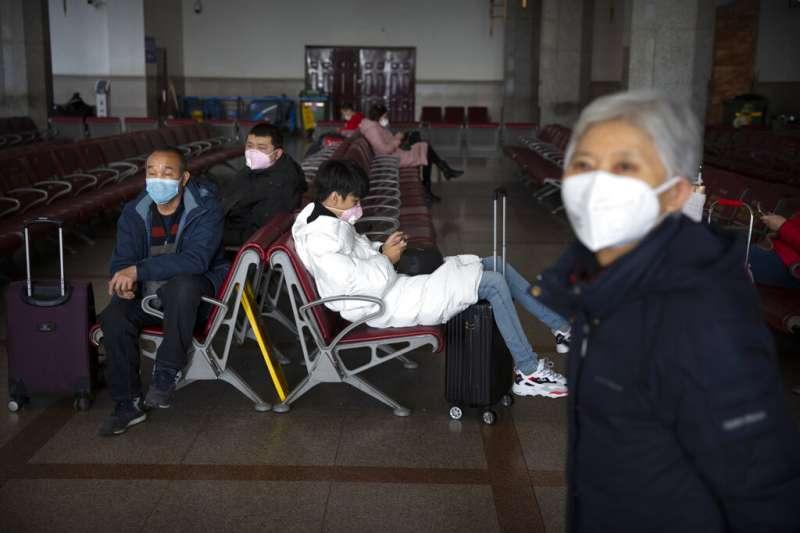 武漢肺炎疫情未歇,北京車站的旅客依舊戴著口罩。(美聯社)
