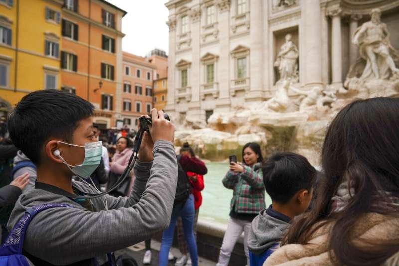 武漢肺炎疫情未歇,中國遊客在義大利羅馬也戴著口罩旅遊。(美聯社)