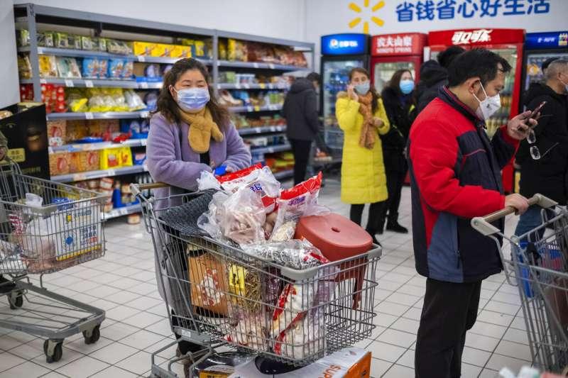 武漢肺炎爆發後,已被封城的武漢居民正在排隊購買日常用品。(美聯社)