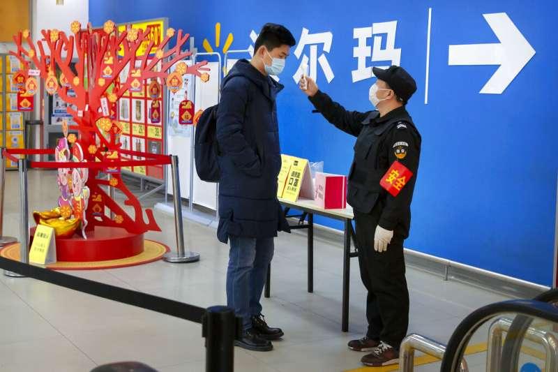 武漢肺炎疫情持續升高,北京沃爾瑪賣場的員工對顧客進行體溫檢測。(美聯社)