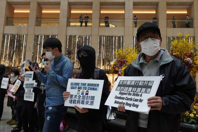 武漢肺炎疫情肆虐,每日有大量中國旅客進入的香港至今未能全面封關,多位香港民眾手持標語抗議。(資料照,美聯社)