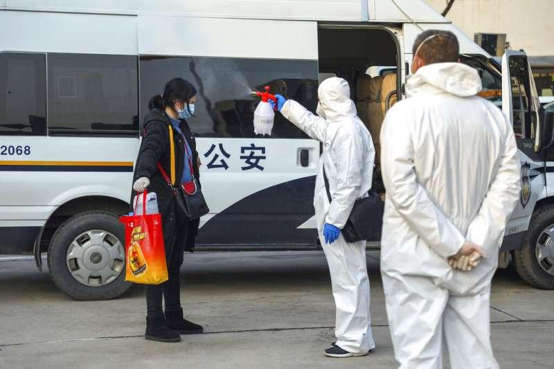 一位到隔離旅館探望親友的武漢市民接受檢疫人員消毒。(美聯社)