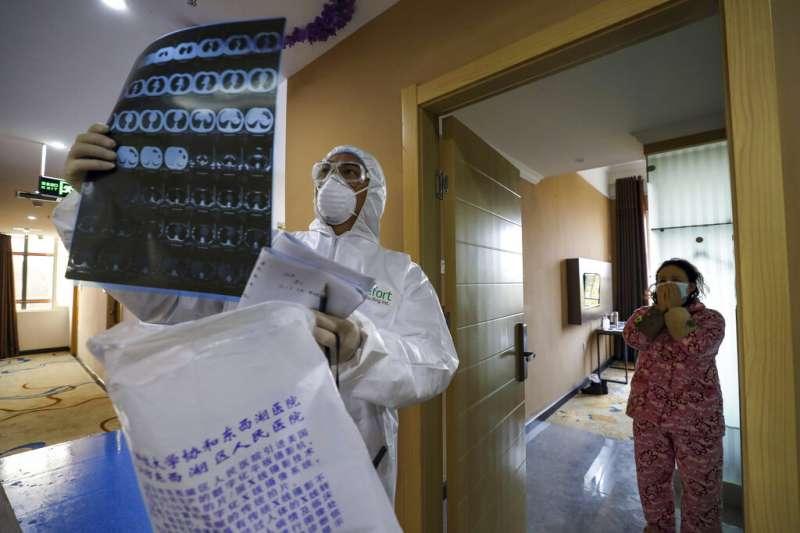 武漢一間收容隔離病患的旅館,身著全套防護服的工作人員正在檢視X光片。(美聯社)