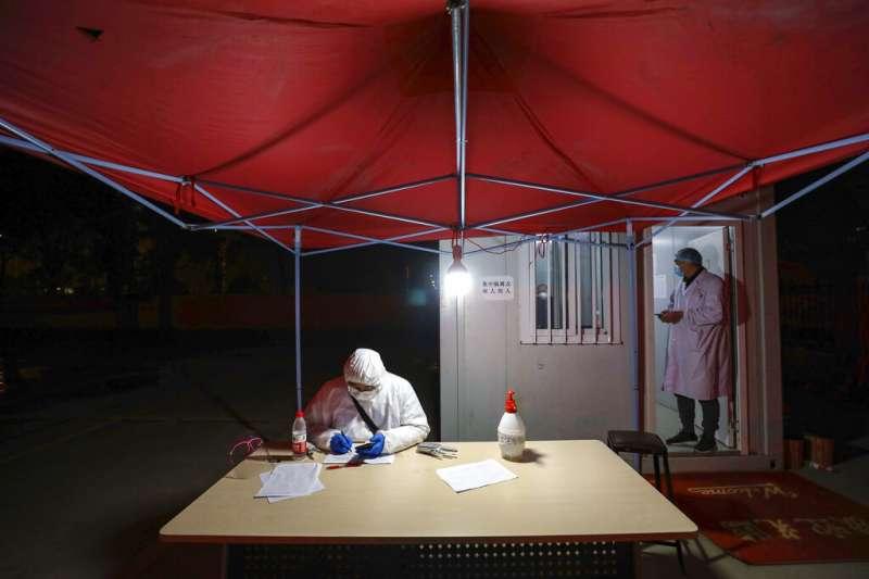 身著全套防護服的工作人員在武漢一間收容隔離病患的旅館外整理資料。(美聯社)