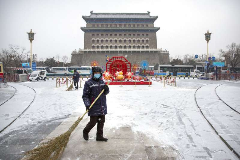 武漢肺炎持續肆虐,中國街頭的行人與掃地工都戴起口罩。(美聯社)