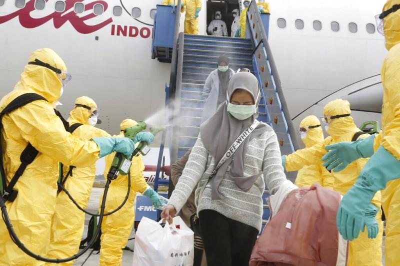 武漢肺炎疫情失控,各國紛紛撤僑,圖為印尼的檢疫人員對從武漢撤回的僑民進行消毒。(美聯社)