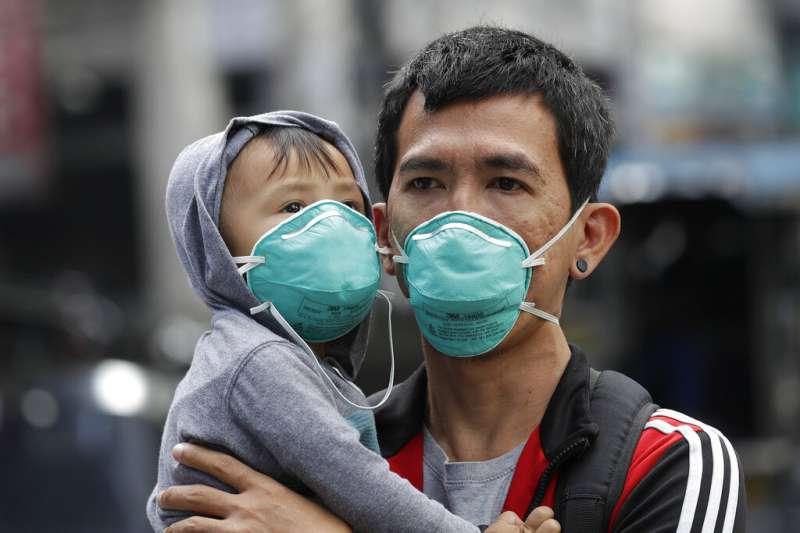 武漢肺炎疫情肆虐,菲律賓馬尼拉街頭一位父親跟他的孩子都戴著口罩,不敢掉以輕心。(美聯社)