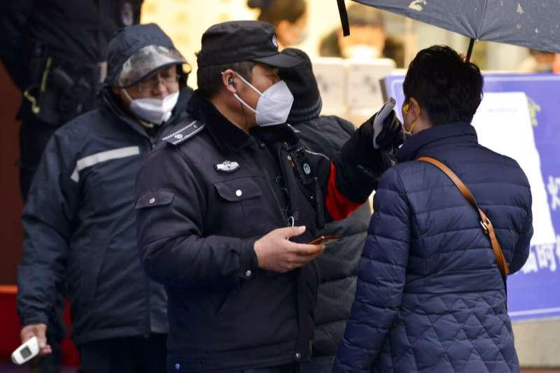 武漢肺炎疫情肆虐,南京市4日晚間發布公告全面實行「小區封閉管理」。圖為警察在秦淮區為往來民眾檢查體溫。(美聯社)