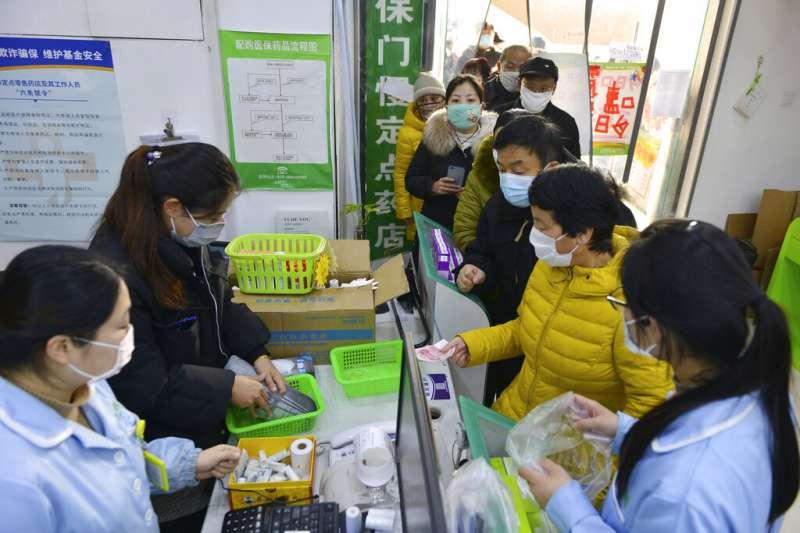 武漢肺炎疫情肆虐,南京市4日晚間發布公告全面實行「小區封閉管理」。圖為南京民眾正在搶購口罩。(美聯社)