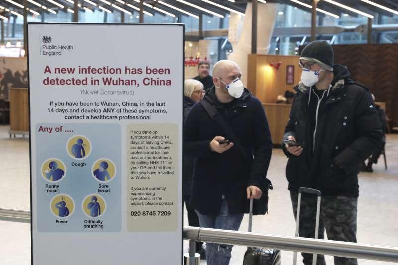 中國武漢肺炎疫情延燒,英國倫敦機場的民眾戴著口罩自保(美聯社)