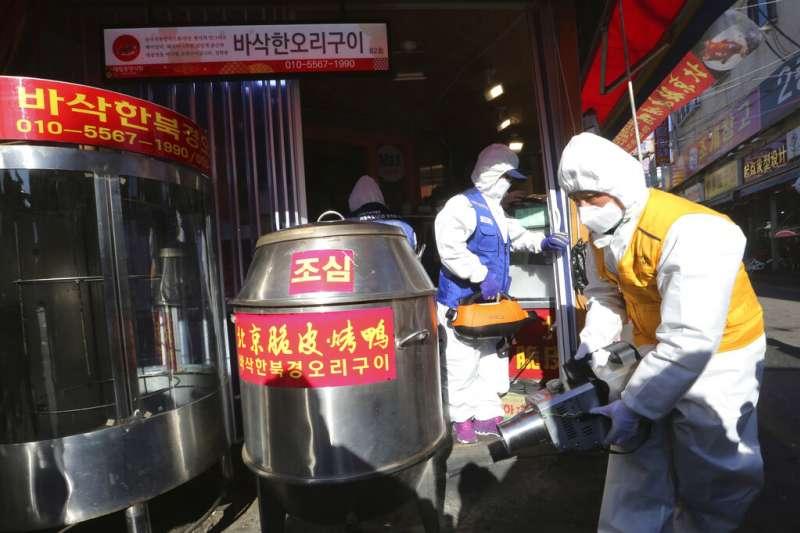 武漢肺炎疫情持續延燒,南韓首爾加強對公共場所的消毒工作。圖為工作人員正在替一間中國烤鴨店消毒。(美聯社)