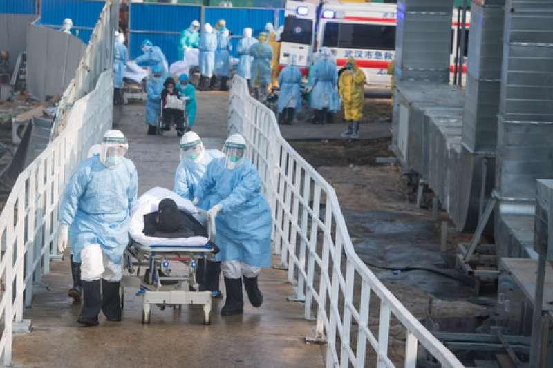 2020年2月4日,武漢肺炎疫情,醫護人員將患者轉運至武漢火神山醫院病房。(新華社)