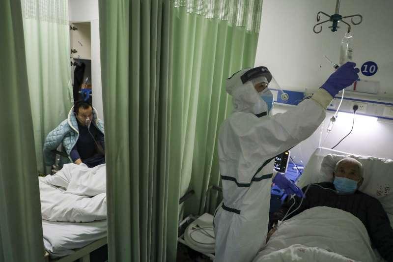 針對首批搭乘武漢包機返台的旅客中有1名台商確診武漢肺炎,武漢市台辦8日提出7大疑點。圖為武漢醫院救治病患。(美聯社)