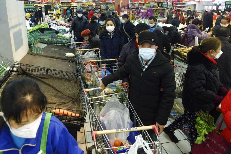 武漢肺炎肆虐,浙江杭州一間超市擠滿了戴著口罩前來搶購生活物品的民眾。(美聯社)