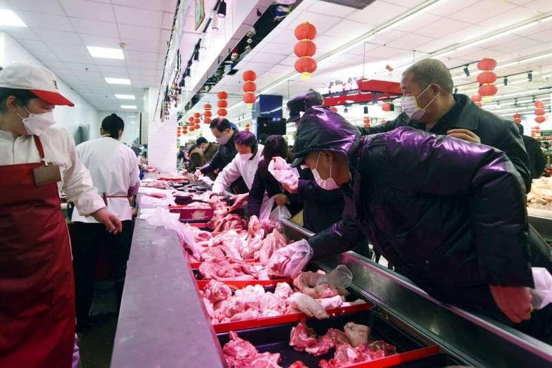 武漢肺炎肆虐,浙江杭州一間超市擠滿了戴著口罩前來搶購食物的民眾。(美聯社)
