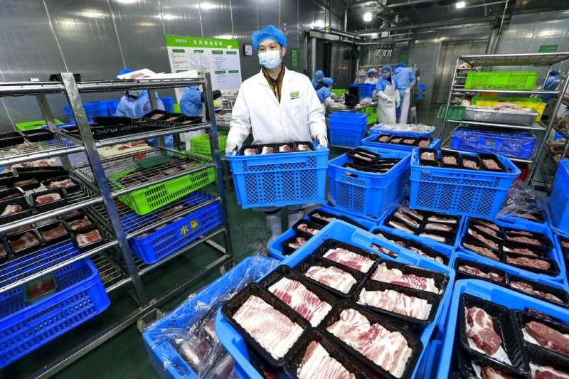 武漢肺炎疫情肆虐,許多中國民眾都忙著搶購生活物資。四川遂寧一間超市正在包裝肉片。(美聯社)