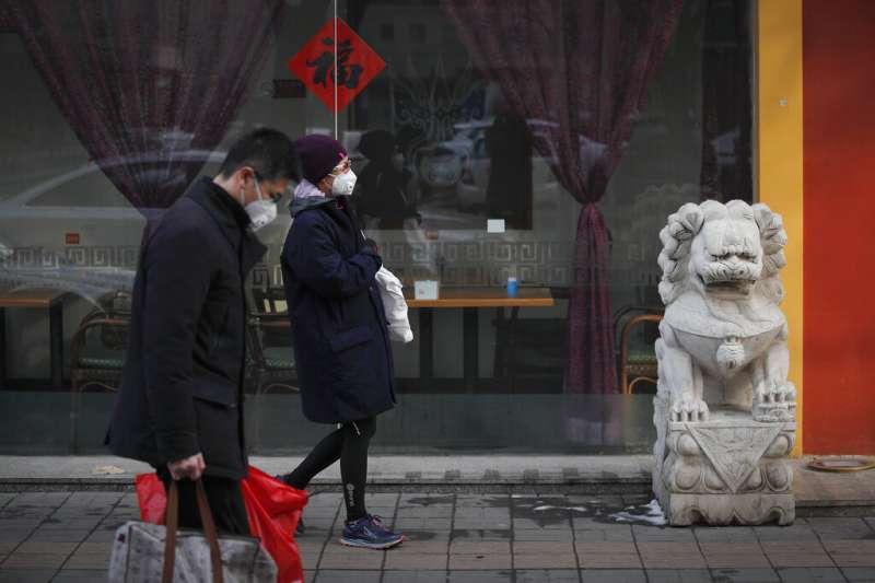 北京街頭的民眾戴著口罩出外採買。(美聯社)