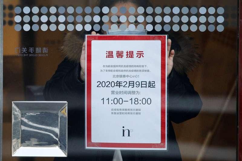 因應武漢肺炎疫情肆虐,北京一間商場貼出營業時間調整的告示。(美聯社)