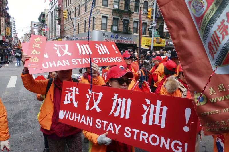 武漢肺炎疫情肆虐,紐約中國城的僑民在元宵節慶祝活動中高舉武漢加油標語。(美聯社)
