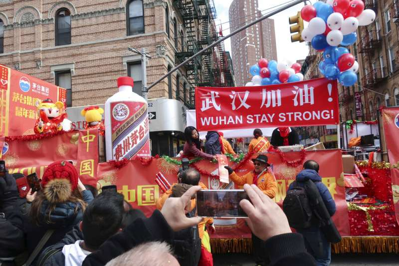 武漢肺炎疫情肆虐,紐約中國城的僑民在元宵節慶祝活動中高舉武漢加油標語與中國國旗。(美聯社)