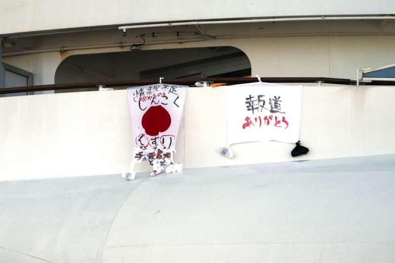 鑽石公主號目前仍有三千多人在船上隔離,船內乘客掛出「藥物不足」、「感謝報導」等標語。(美聯社)