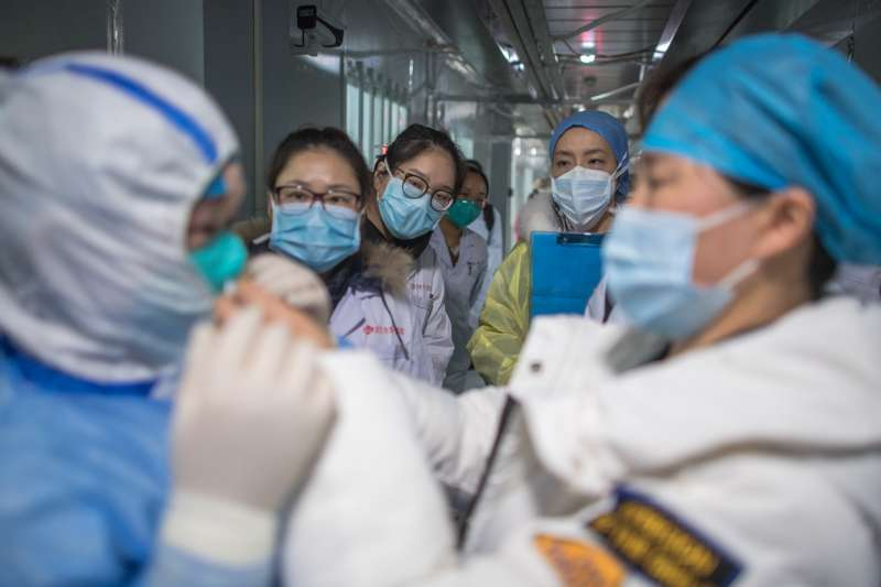 2020年2月8日,在武漢雷神山醫院,護士在觀看示範防護服的穿戴。(新華社)