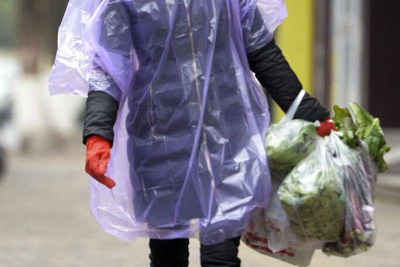 武漢肺炎疫情持續延燒,武漢一位居民全副武裝上街買菜。(美聯社)
