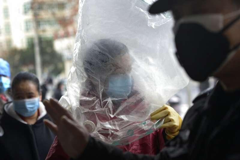 武漢肺炎疫情持續延燒,武漢一位民眾上街買菜乾脆用塑膠袋把自己的頭整個套住。(美聯社)