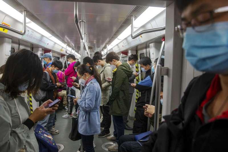 武漢肺炎疫情肆虐,已經宣布「封閉式管理」的廣州地鐵乘客全都戴著口罩。(美聯社)