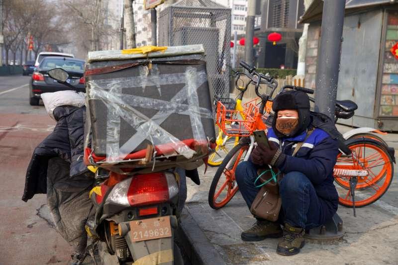 北京一位快遞員正在路邊休息。北京目前採取「封閉式管理」,許多市民都要仰賴外送採買生活所需。(美聯社)