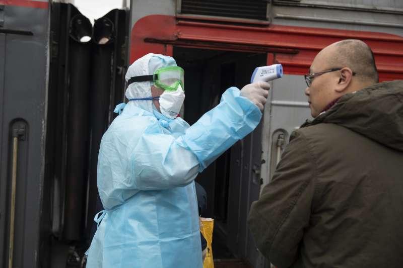 1月31日,俄羅斯莫斯科火車站,一名醫護人員正為來自中國北京的乘客量體溫(美聯社)