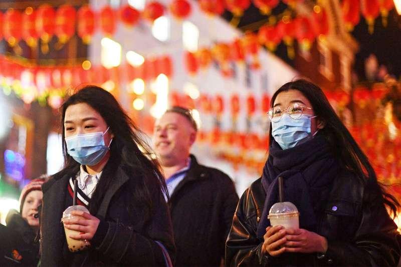 中國武漢肺炎疫情蔓延,許多國家傳出華人遭騷擾、辱罵甚至暴力相向情形。圖為英國倫敦中國城的人們戴著口罩。(美聯社)