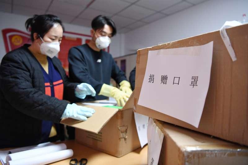 武漢肺炎疫情,中國工作人員清點愛心人士捐贈的醫用口罩。(新華社)