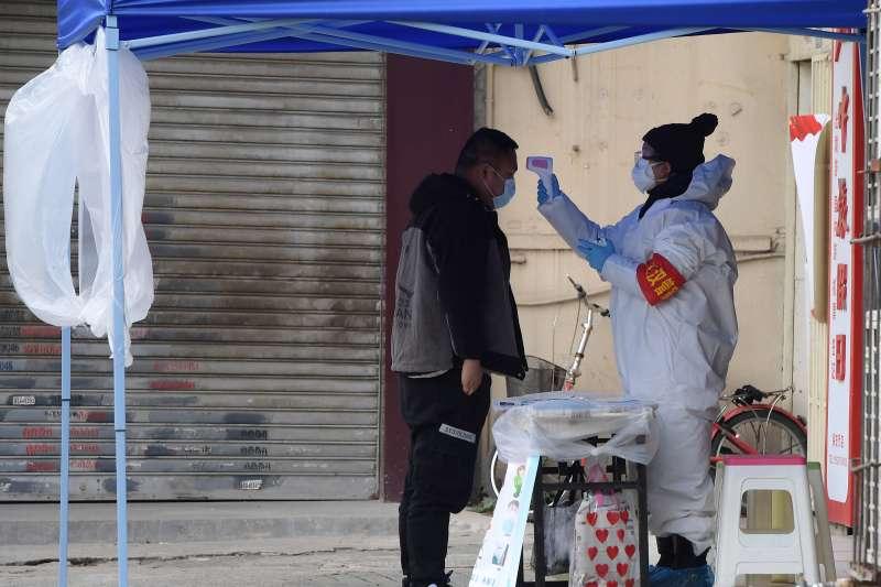 武漢肺炎疫情,2020年2月10日,武漢市園林局支援德望社區的一位下沉工作人員在值守的社區門口為來訪者測量體溫。(新華社)