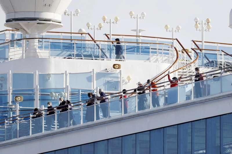 因多人群聚感染、停泊日本遭隔離的郵輪「鑽石公主號」,乘客在甲板上向下張望。(AP)