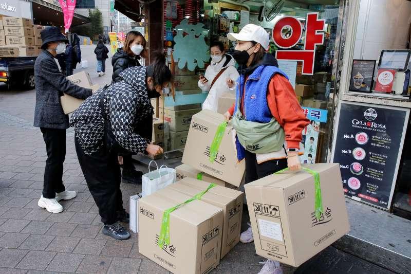 上月底,在明洞一間藥房外可見有遊客大批購入口罩。(圖片來源:路透社/*CUP提供)