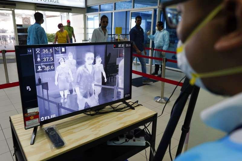 武漢肺炎肆虐,馬來西亞海關的檢疫人員也為往來旅客測量體溫。(美聯社)