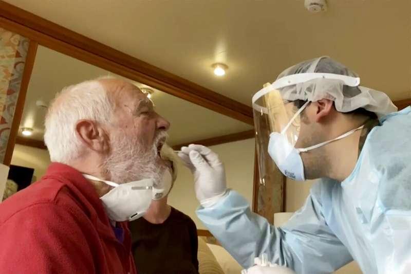 一名從中國返台進行居家檢疫的台商表示,自己居家檢疫14天,可能「沒人」知道。圖為日本檢疫官正在為民眾採集檢體。(資料照,美聯社)