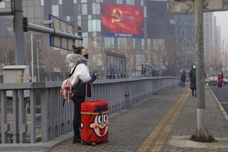 旅程、旅人、旅遊、旅行、旺旺、旺中。北京街頭戴著口罩的一位女性。(美聯社)