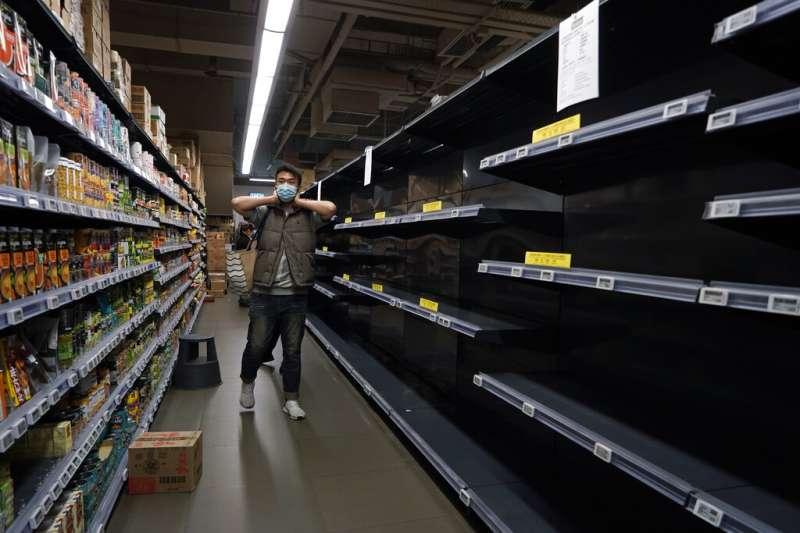 武漢肺炎肆虐,香港商場貨架上民生物資都被搶購一空。(美聯社)