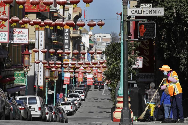 武漢肺炎疫情延燒,美國加州舊金山的唐人街,一名清潔人員戴著口罩清掃街道(美聯社)
